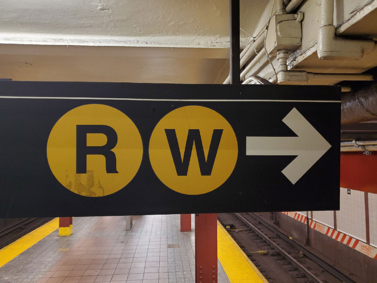A wayfinding sign for the R and W trains in a New York City subway station